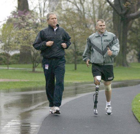 A veteran who lost part of his right leg in Afghanistan jogs with President Bush
